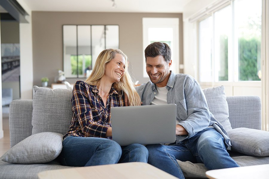 couple smiling looking computer 900x